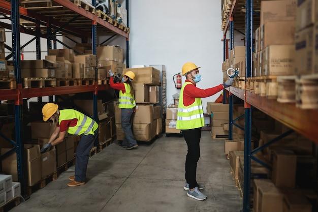 Lavoratori industriali all'interno del magazzino che indossano maschere di sicurezza per la prevenzione del coronavirus - focus sull'uomo