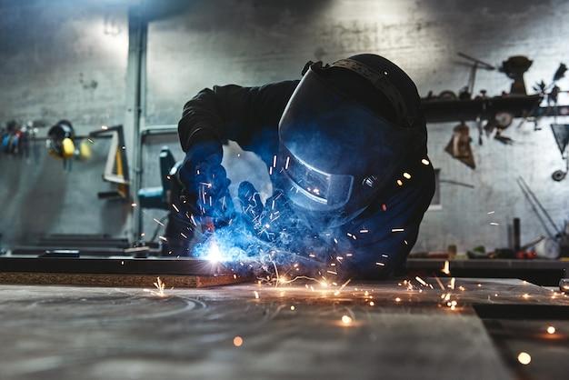 Operaio industriale che indossa casco e guanti che saldano la costruzione in acciaio in fabbrica