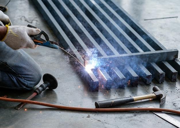 Operaio industriale che salda acciaio con scintille