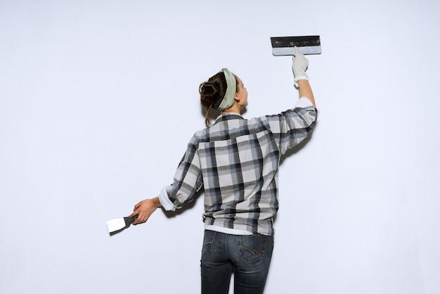 Industriosa giovane donna builder che fa riparazioni in appartamento, livellando le pareti con una spatola