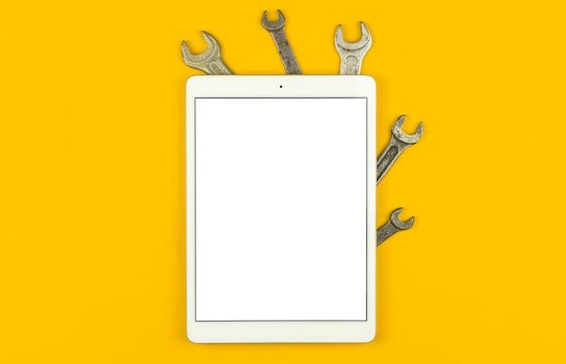 Modello di industria e costruzione con tablet, schermo bianco vuoto, tavolo con kit di attrezzi, sfondo giallo, vista dall'alto, disposizione piatta e foto dello spazio di copia