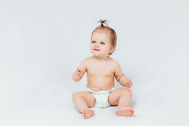 Neonata del bambino neonato in pannolino che si trova seduta sorridente felice su un muro bianco