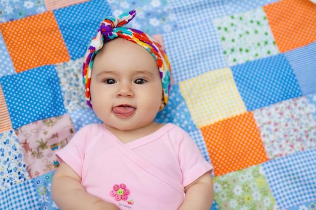 Un neonato giace su una trapunta patchwork e mostra la sua lingua.