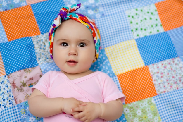 Un neonato giace su una trapunta patchwork con uno sguardo sorpreso.