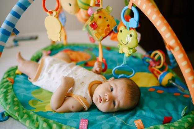 Il bambino giace su un tappetino da gioco e tiene in mano un sonaglio