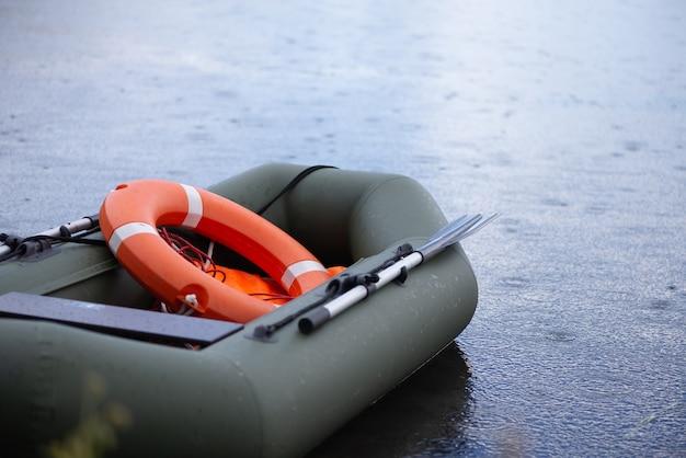 Scialuppa di salvataggio gonfiabile con un salvagente a bordo galleggia nel lago durante la pioggia