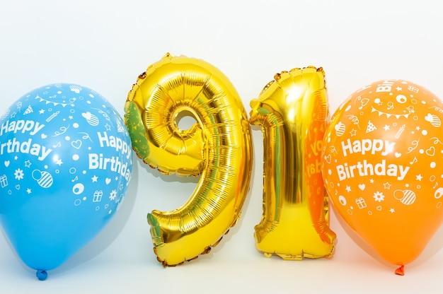 Numero gonfiabile 91 scintillante colore dorato metallizzato con palloncini blu e gialli isolati su priorità bassa bianca.