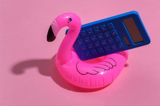 Fenicottero rosa gonfiabile e calcolatrice su sfondo rosa soleggiato. concetto di vacanza estiva. minimalismo