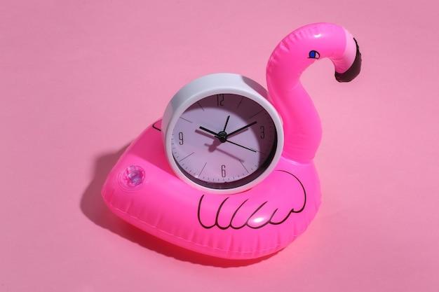 Fenicottero rosa gonfiabile e orologio su sfondo rosa soleggiato. concetto di vacanza estiva. minimalismo