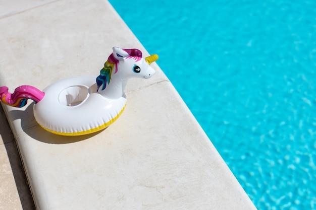Unicorno gonfiabile rosa mini arcobaleno, cocktail stand vicino alla piscina in una luminosa giornata di sole, copia dello spazio.