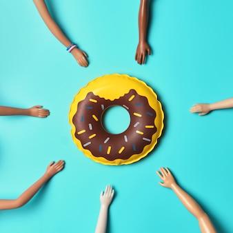Giocattolo galleggiante per piscina gonfiabile e sette mani di bambola di diversi colori della pelle sulla superficie blu