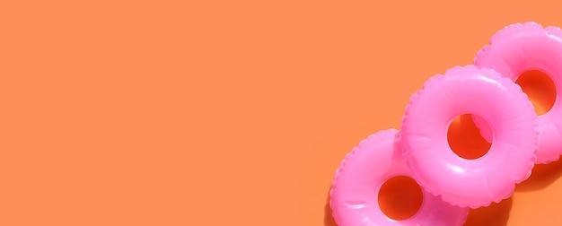 Anelli gonfiabili su sfondo arancione. concetto di sfondo estivo