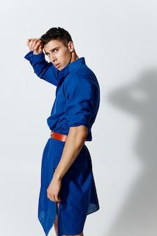 Torso gonfiato di un uomo con un vestito blu e con una cintura rossa su uno sfondo chiaro ritratto ritagliato