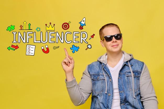 Concetto dell'influencer - il giovane tipo sorride su spazio giallo.
