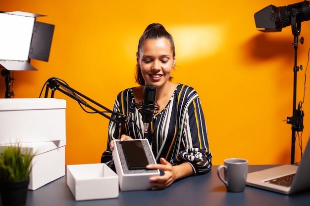 Influencer che presenta il telefono per l'omaggio durante il podcast