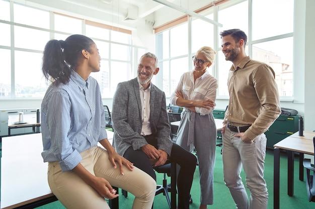 Conversazione informale team aziendale multirazziale di successo che parla nell'ufficio moderno discutendo