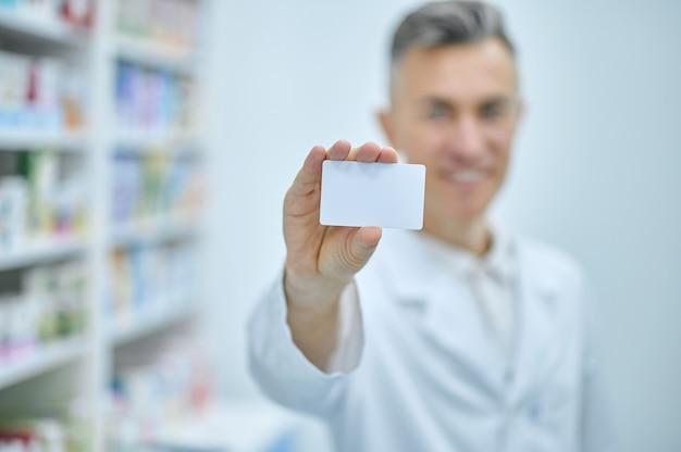 Informazione, attenzione. carta in mano tesa di un uomo sorridente in camice bianco da medico nella stanza della farmacia