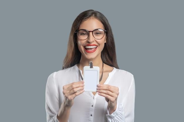 Informazioni, badge. giovane donna dai capelli lunghi con gli occhiali e in camicetta bianca che mostra il distintivo con gioia