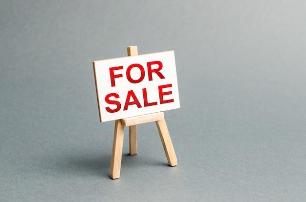 Stand informativo con una scritta in vendita annuncio della vendita e attrazione di acquirenti