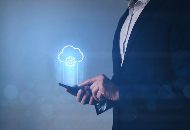 Tecnologo dell'informazione che tiene il telefono con l'icona di cloud computing.