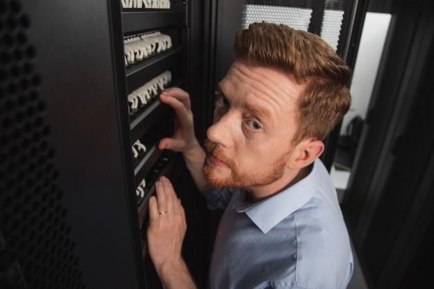Tecnologie dell'informazione. vista dall'alto di un tecnico it esperto che esamina l'armadio del server mentre guarda la fotocamera