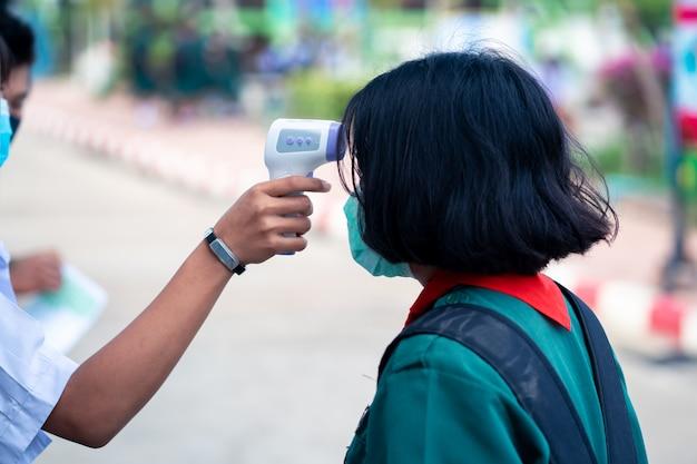Test della temperatura della fronte della pistola del termometro a infrarossi per controllare lo studente