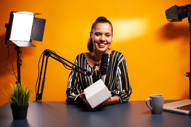 Infuencer presenta regalato alla telecamera durante la registrazione di vlog in home studio