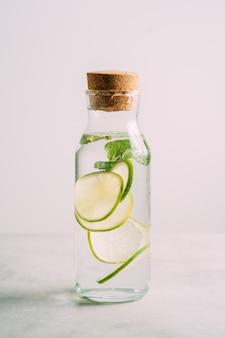 Acqua della disintossicazione infusa con calce e la menta in una bottiglia sulla tavola bianca.