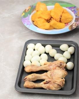 Ingrediente di opor ayam tofu, pollo al curry dall'indonesia con tofu giallo e uovo di quaglia