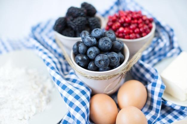 Ingredienti per cuocere torte dolci con frutti di bosco.