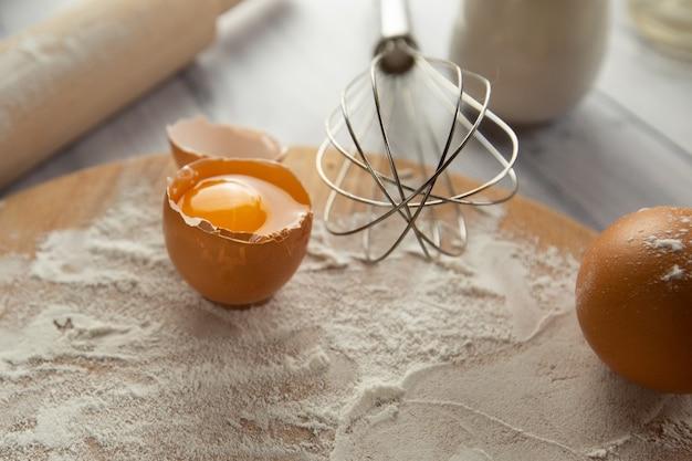Gli ingredienti per la cottura in tavola sono farina di frumento su una tavola uova latte e una frusta