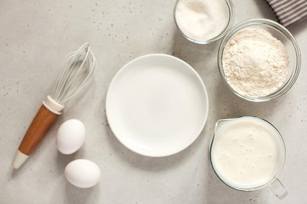 Ingredienti per cuocere con farina e una frusta da cucina con un piatto bianco vuoto