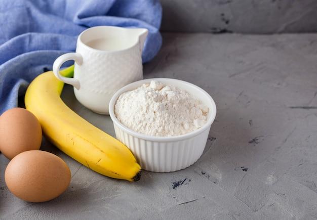 Gli ingredienti per la torta di banana sulla superficie grigia. cucchiaio di legno, banana, uova, latte