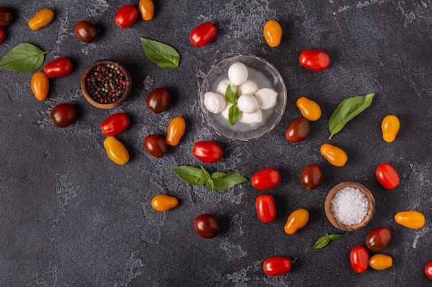 Ingredienti per insalata caprese: pomodori, mozzarella e basilico, vista dall'alto.