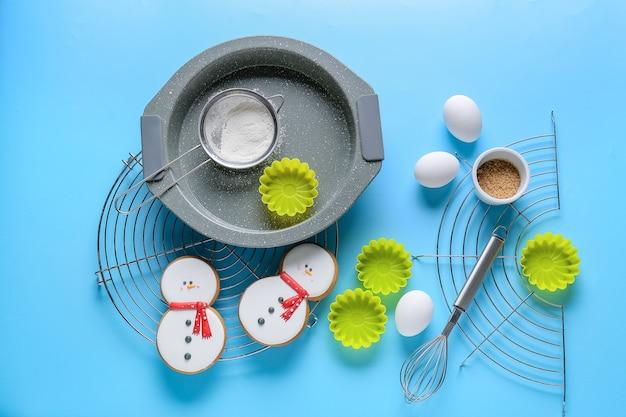 Ingredienti per la pasticceria di natale e gli utensili da cucina su sfondo colorato