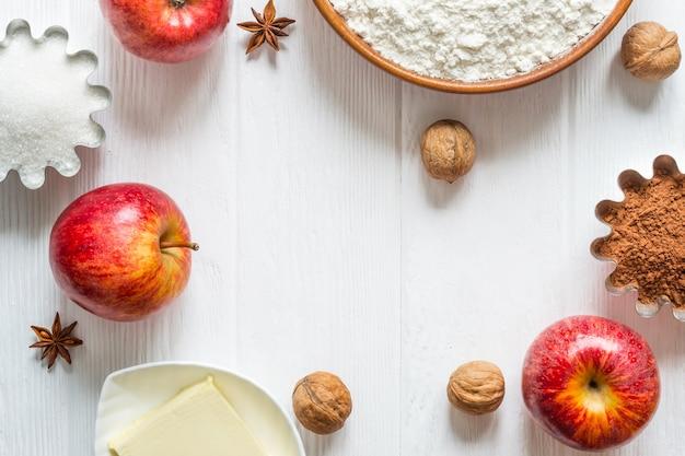 Ingredienti per la cottura di natale su sfondo bianco. cornice fatta di farina, mele, noci e spezie