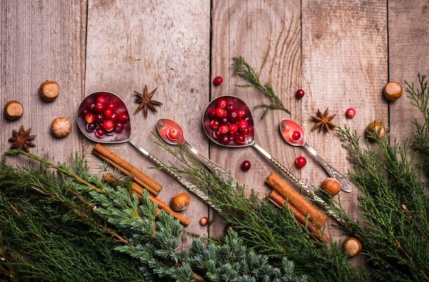 Ingredienti per natale, biscotti da forno invernali. pan di zenzero, torta di frutta, bevande di stagione. mirtilli, arance secche, cannella, spezie su una tavola di legno, vista superiore dello spazio della copia.
