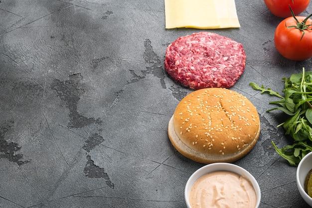 Ingredienti per la cottura degli hamburger. polpette di manzo macinata, panini, pomodori, erbe aromatiche e spezie, su tavola di pietra grigia