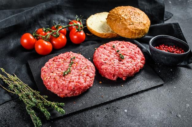 Ingredienti per cucinare hamburger. tortini di carne macinata, focacce, pomodori, erbe e spezie. vista dall'alto