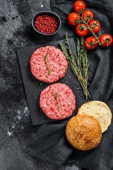 Ingredienti per cucinare hamburger. tortini di manzo macinato, focacce, pomodori, erbe e spezie
