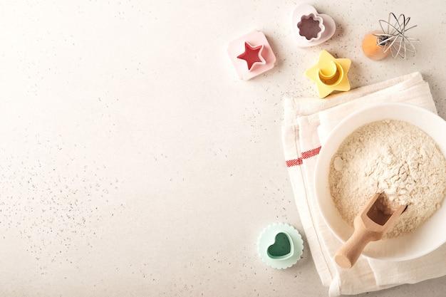 Ingredienti per cucinare la cottura fatta in casa. sfondo di cottura con farina, uova, utensili da cucina, utensili e stampi per biscotti sul tavolo di marmo bianco. vista dall'alto. stile piatto. modello.