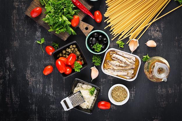 Ingredienti per la cottura della pasta spaghetti alla puttanesca - piatto di pasta italiano con pomodori, olive nere, capperi, acciughe e prezzemolo. vista dall'alto, posizione piatta