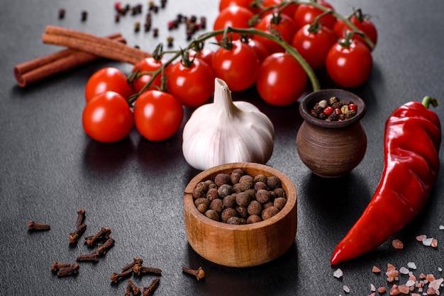 Ingredienti per cucinare, spezie, aglio, pomodori ed erbe su sfondo nero