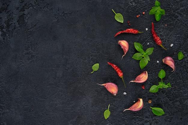 Ingredienti per cucinare. vista dall'alto di aglio, basilico e peperoncino sul tavolo scuro.