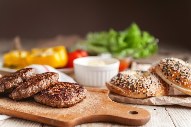 Ingredienti per un delizioso hamburger di casa. rotolo, bagel, con una succosa cotoletta di manzo, salse formaggio foglie fresche di lattuga