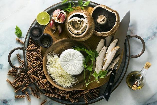 Ingredienti per la cottura senza glutine di pasta fusilli da farina di farro a grana grossa con funghi portobello e ricotta su un vassoio su un tavolo di marmo. cucinare ricette sane