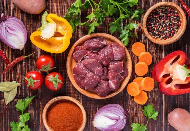 Ingredienti per la cottura di gulasch o stufato: carne cruda, erbe, spezie, verdure su fondo di legno scuro.