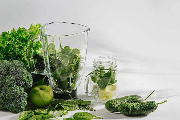 Ingredienti per frullati verdi in un frullatore. concetto di cibo sano con spinaci e verdure verdi. cibo vegetariano.