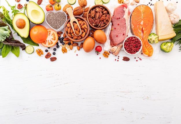 Ingredienti per la selezione di cibi sani su fondo di legno bianco.