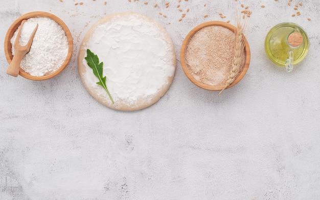 Gli ingredienti per l'impasto della pizza fatta in casa con spighe di grano, farina di grano e chicchi di grano allestiti su sfondo di cemento bianco.